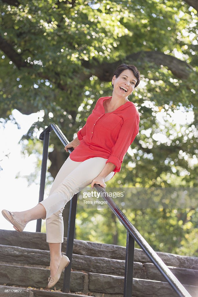 USA, New York State, New York City, Mature woman sliding down railing in park