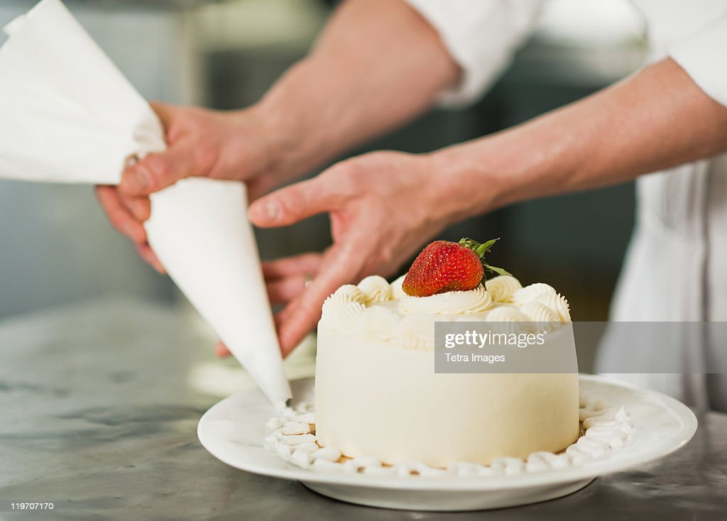 USA, New York State, New York City, Pastry chef decorating cake