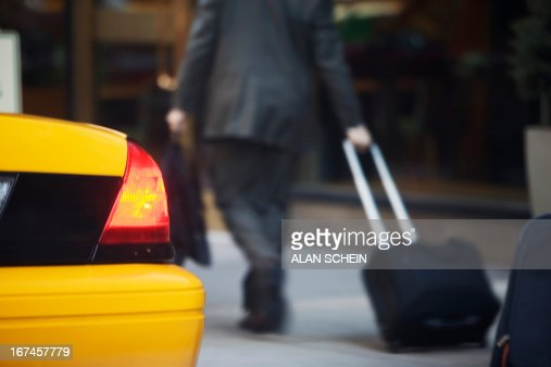 USA, New York State, New York City, Rear view of businessman pulling suitcase by yellow taxi : Stock Photo