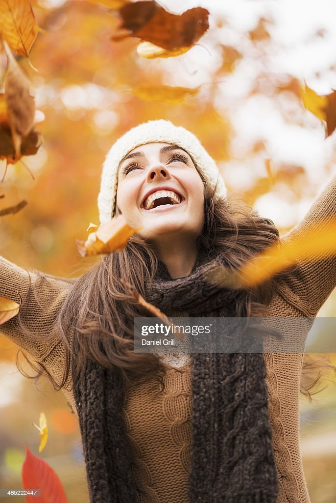 USA, New York State, New York City, Young woman playing with leaves in Central Park