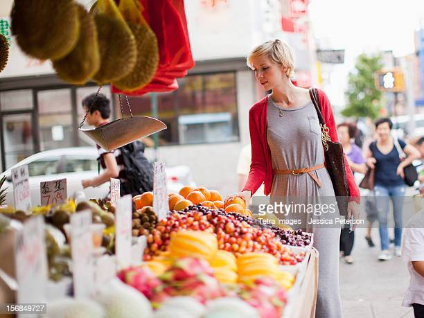 USA, New York State, New York, Woman looking at fresh friuts at street market.