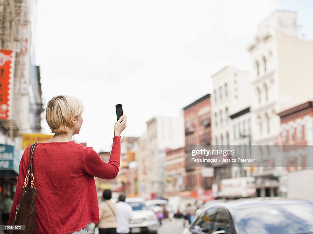 USA, New York State, New York, Woman taking picture with her mobile phone on street.