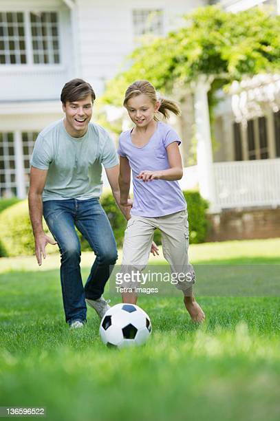 USA, New York State, Old Westbury, Father and daughter (10-11) playing soccer
