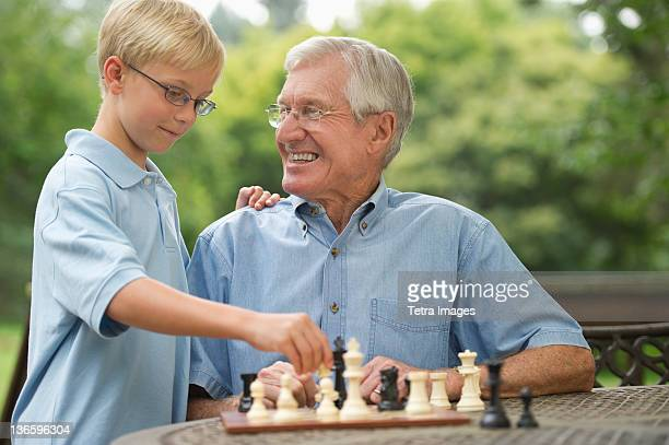USA, New York State, Old Westbury, Grandfather and grandson (10-11) playing chess on porch