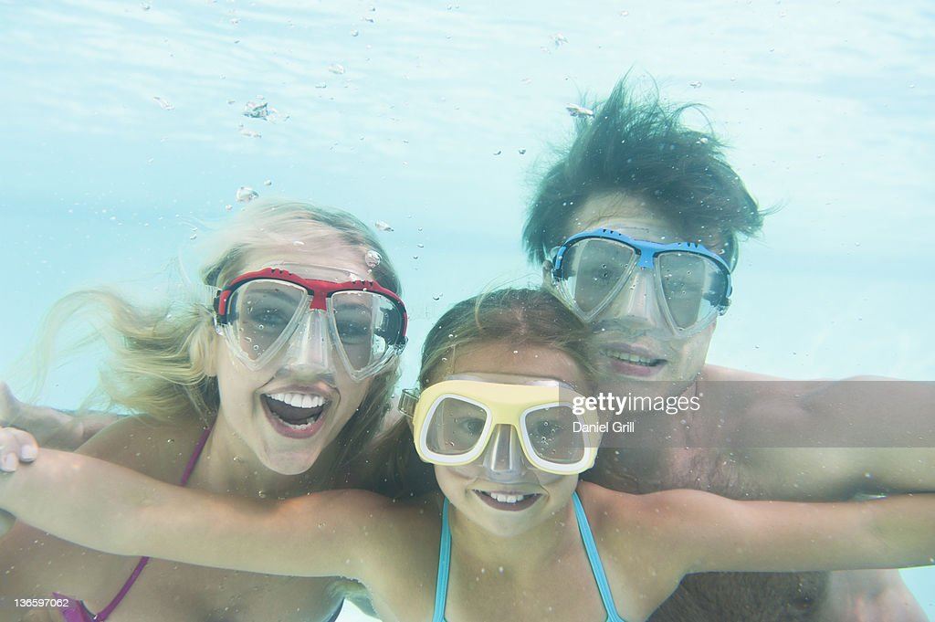 USA, New York State, Old Westbury, Parents with daughter (10-11) swimming underwater : Stock Photo