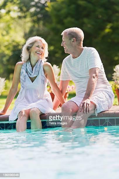 USA, New York State, Old Westbury, Senior couple at edge of swimming pool