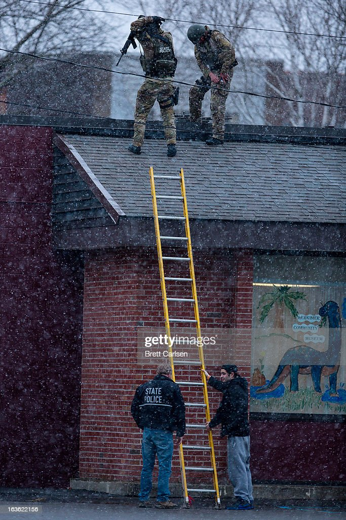 New York State Police officers positioned on a rooftop prepare to descend a ladder during a standoff with murder suspect Kurt Meyers on March 13, 2013 in Herkimer, New York. Police have identified 64-year-old Kurt Meyers as a possible suspect responsible for a total of four shooting deaths and two injuries across the area earlier in the day.