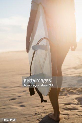 USA, New York State, Rockaway Beach, Female surfer walking on beach at sunset