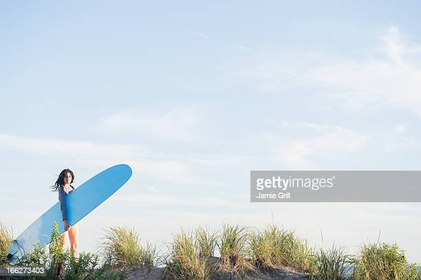 USA, New York State, Rockaway Beach, Female surfer walking on beach
