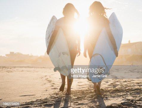 USA, New York State, Rockaway Beach, Two female surfers walking on beach at sunset