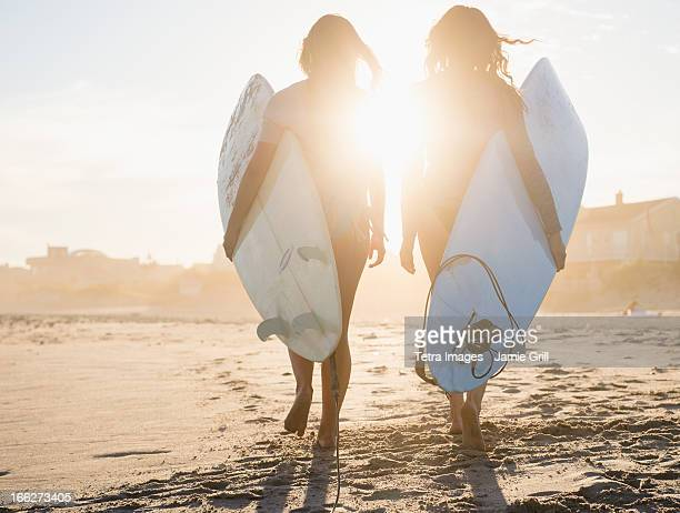 USA, New York State, Rockaway Beach, Two female surfers walking on beach at sunset