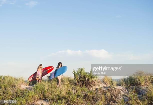 USA, New York State, Rockaway Beach, Two female surfers walking on beach