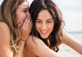 USA, New York State, Rockaway Beach, Two women whispering on beach