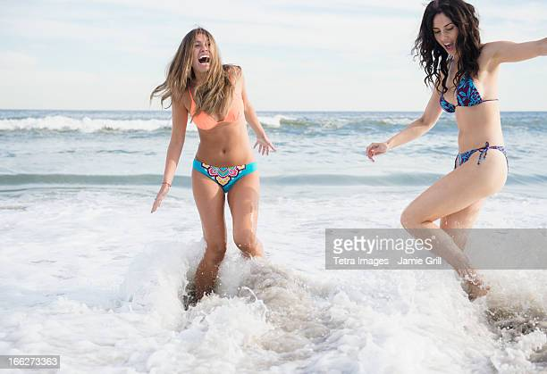 USA, New York State, Rockaway Beach, Two young women jumping in sea