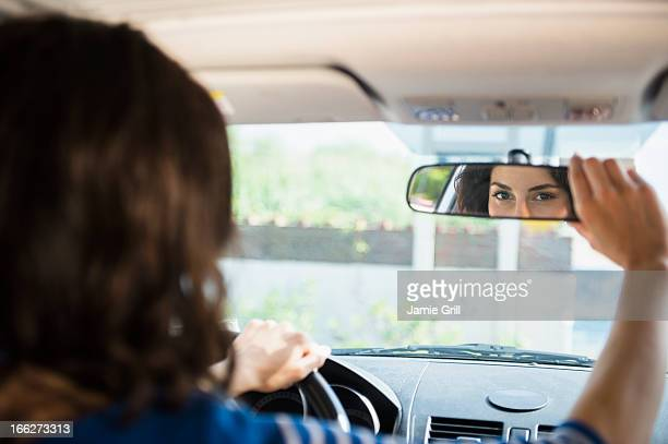 USA, New York State, Rockaway Beach, Woman adjusting rear view mirror in car