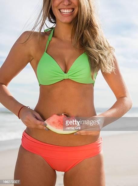USA, New York State, Rockaway Beach, Woman eating watermelon at beach