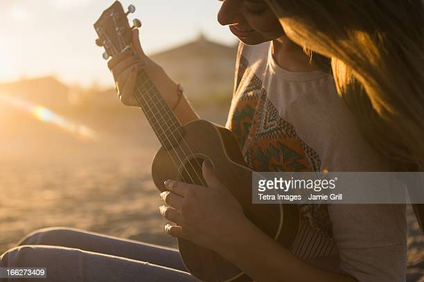 USA, New York State, Rockaway Beach, Woman playing ukulele at sunset