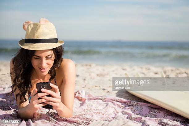 USA, New York State, Rockaway Beach, Woman using cell phone on beach