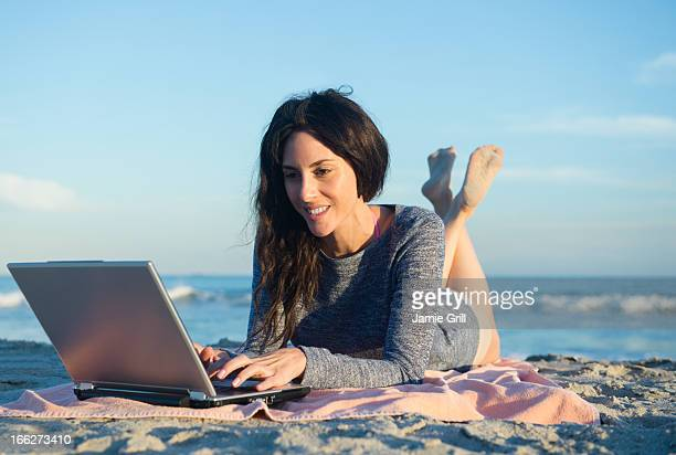 USA, New York State, Rockaway Beach, Woman using laptop on beach