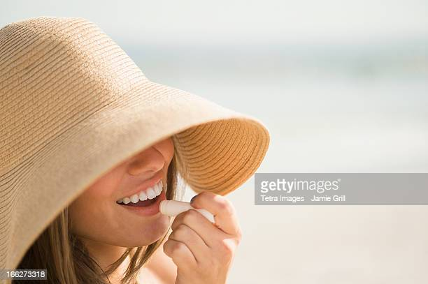 USA, New York State, Rockaway Beach, Woman wearing sun hat applying lipstick