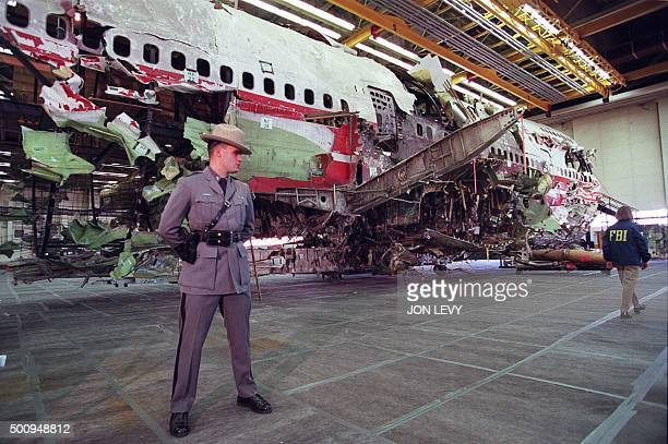 A New York State trooper stands guard 19 November in front of the reconstructed wreckage of the Boeing 747 aircraft that was TWA flight 800 in...