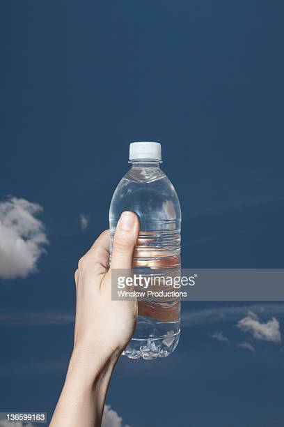 USA, New York State, Woman's hand holding water bottle against sky