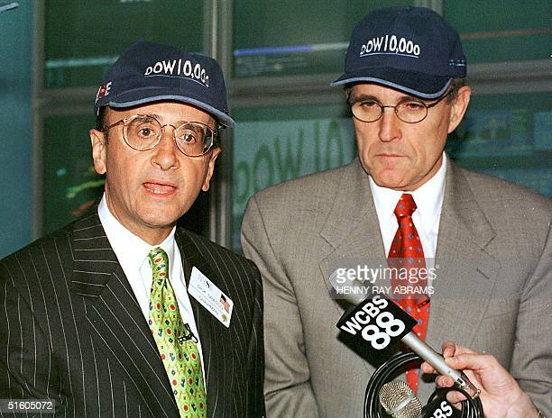 New York Stock Exchange Chairman Richard Grasso and New York City Mayor Rudy Giuliani wear 'Dow 10000' hats They answered questions after the Dow...