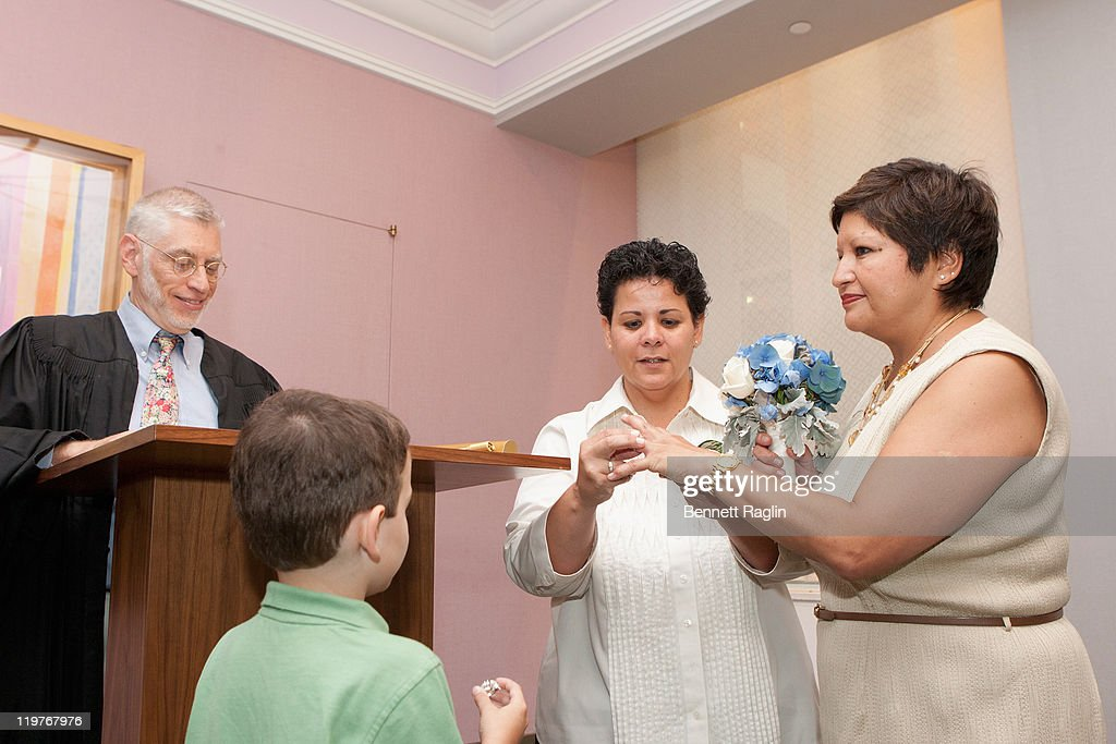 New York Supreme Court Judge Mike Stallman officates the wedding of Diana Leddy and Jeanette Leddy of New York City as Alex looks on during the first day of legal same-sex marriage in New York State on July 24, 2011 in New York City.