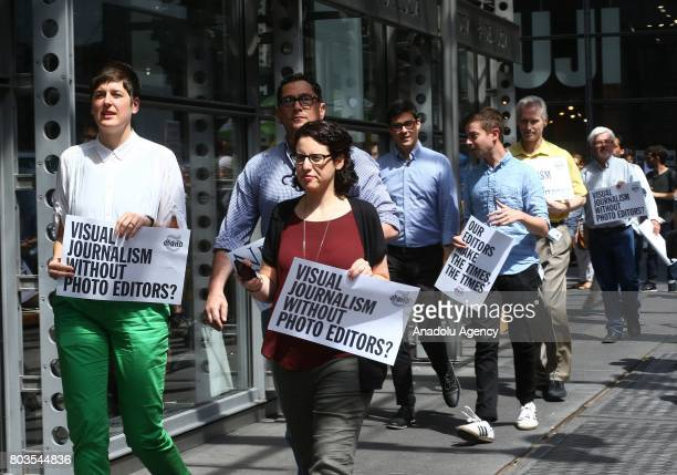 New York Times employees hold banners during a temporary strike against downsizing and dismissal plans of the NYT management outside of New York...