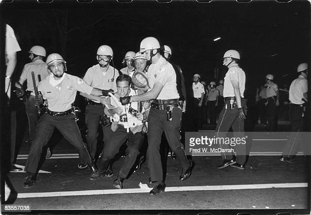 New York Times photographer Barton Silverman struggles to hold onto his cameras as he is arrested by police on Michigan Avenue during the Democratic...