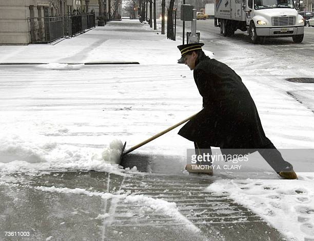 A doorman cleans the sidewalk on Sutton Place on the Upper East Side in New York 16 March 2007 as winter returned to the northeastern United States...