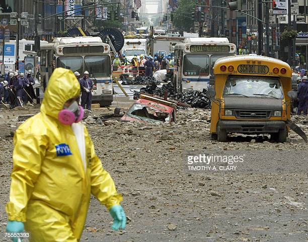 A emergency worker in contamination gear walks near the site of an underground steam pipe explosion 19 July 2007 The 18 July explosion tore a crater...