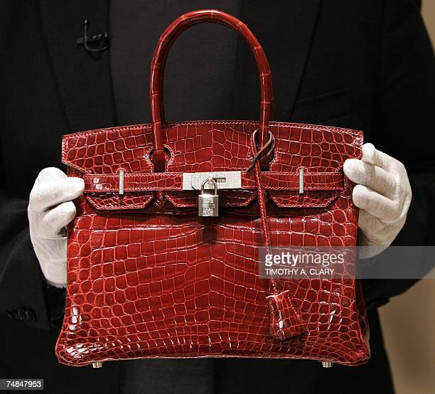 A employee holds a 129000 USD crocodile Hermes Birkin Bag for the press to see during a private opening for the new Hermes store on Wall Street in...
