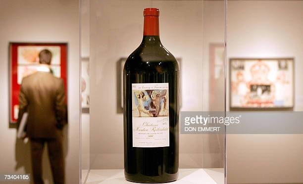 A man looks at paintings created for labels of Chateau Mouton Rothschild 23 February 2007 at Sotheby's in New York The bottle in the middle has a...