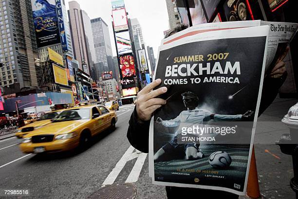 A man poses with a New York Times showing a fullpage advertisement announcing the arrival in summer of 2007 of English soccer star David Beckham to...