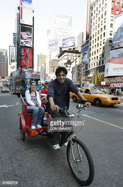 A pedicab rider takes tourists on a ride through Times Square 18 May 2006 in New York Riders take tourists on scenic rides through Central Park and...