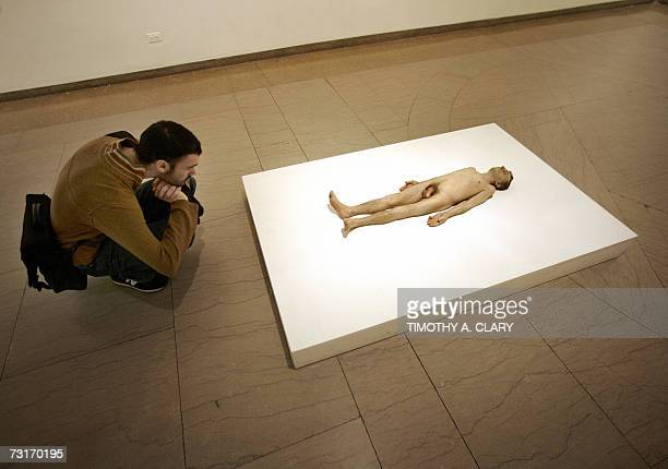 A tourist looks at a sculpture titled 'Dead Dad' by Australianborn artist Ron Mueck at the Brooklyn Museum 31 January 2007 Mueck has on exhibit a...