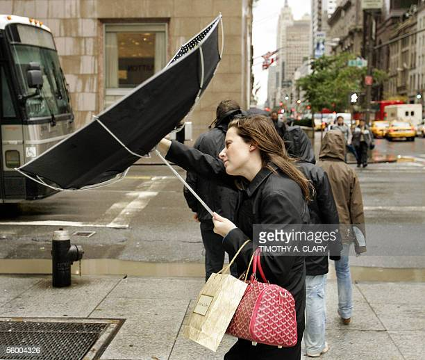 A woman struggles with her umbrella in the wind on New York's 5th Avenue 25 October 2005 as remnants of hurricane Wilma teamed with a 'nor'easter'...