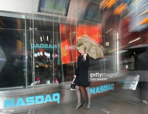 A woman walks past the Nasdaq in Times Square 18 January 2006 in New York Wall Street shares struggled again Wednesday after three losing sessions as...