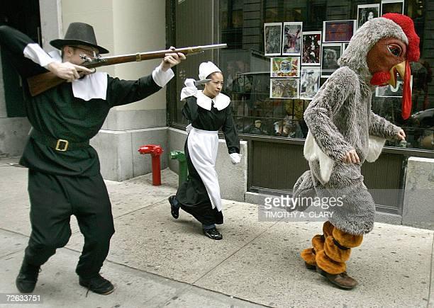 Actors Christine DeLos Angeles and Joseph Buchanan dressed as Pilgrims chase Sixto Cuevas dressed as turkey down the street in New York 22 November...