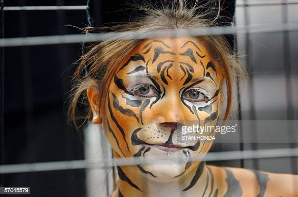 Amy Jannette her nearlynude body painted like a tiger sits in a cage 09 March in New York's Times Square as part of a PETA protest against the use of...