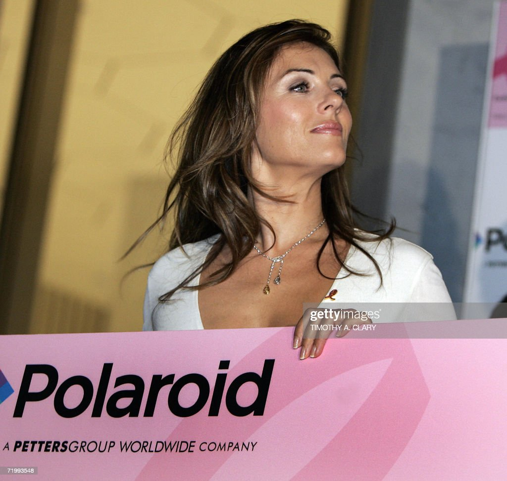 British model and actress Elizabeth Hurley poses with a USD 60000 check from Polaroid along with a special edition Polaroid pink digital camera that...