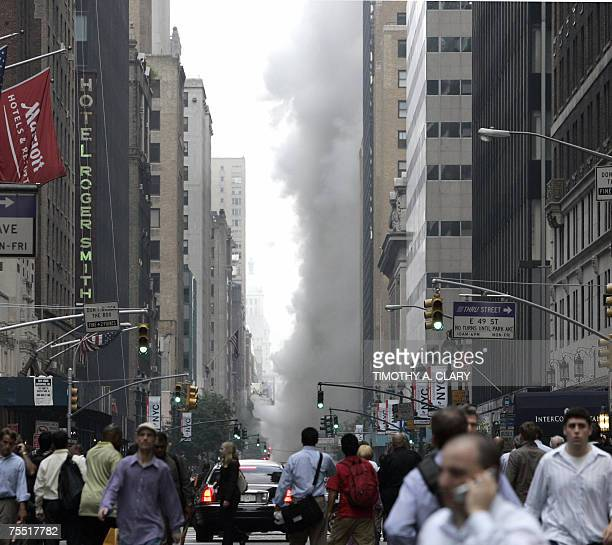 Commuters watch a rising cloud of steam after an underground steam pipe explosion tore through a Manhattan street near Grand Central Terminal during...