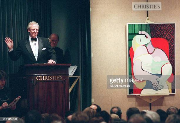 File picture taken 10 November 1997 shows Christopher Burge chairman of Christie's starting the bidding for Pablo Picasso's painting 'Le Reve' in New...