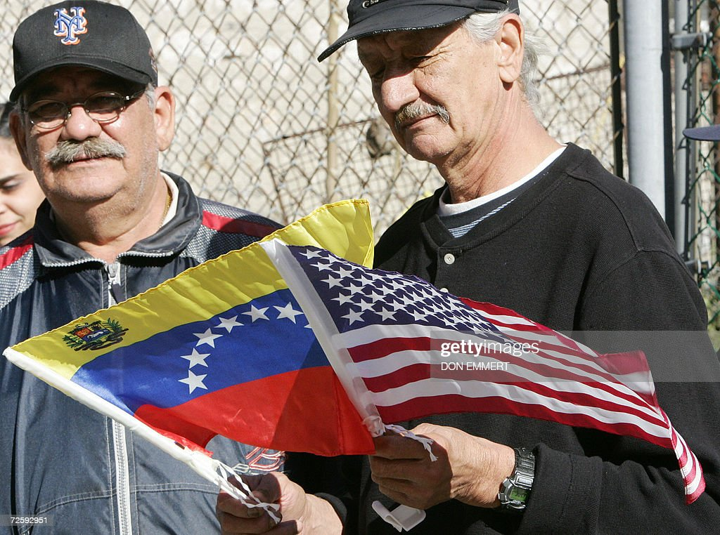 Neighbors of a cooperative apartment building, flying flags of Venezuela and the US, listen to political speeches as low cost heating oil was being delivered to their cooperative apartment building 17 November, 2006 in the Bronx. The delivery was the initial low-cost heating oil of the CITGO-Venezuela heating oil program to the 60-unit building. AFP PHOTO/DON EMMERT