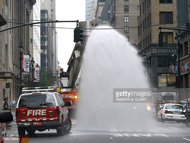 New York City firefighters hose debris after an underground steam pipe explosion tore through a Manhattan street near Grand Central Terminal during...