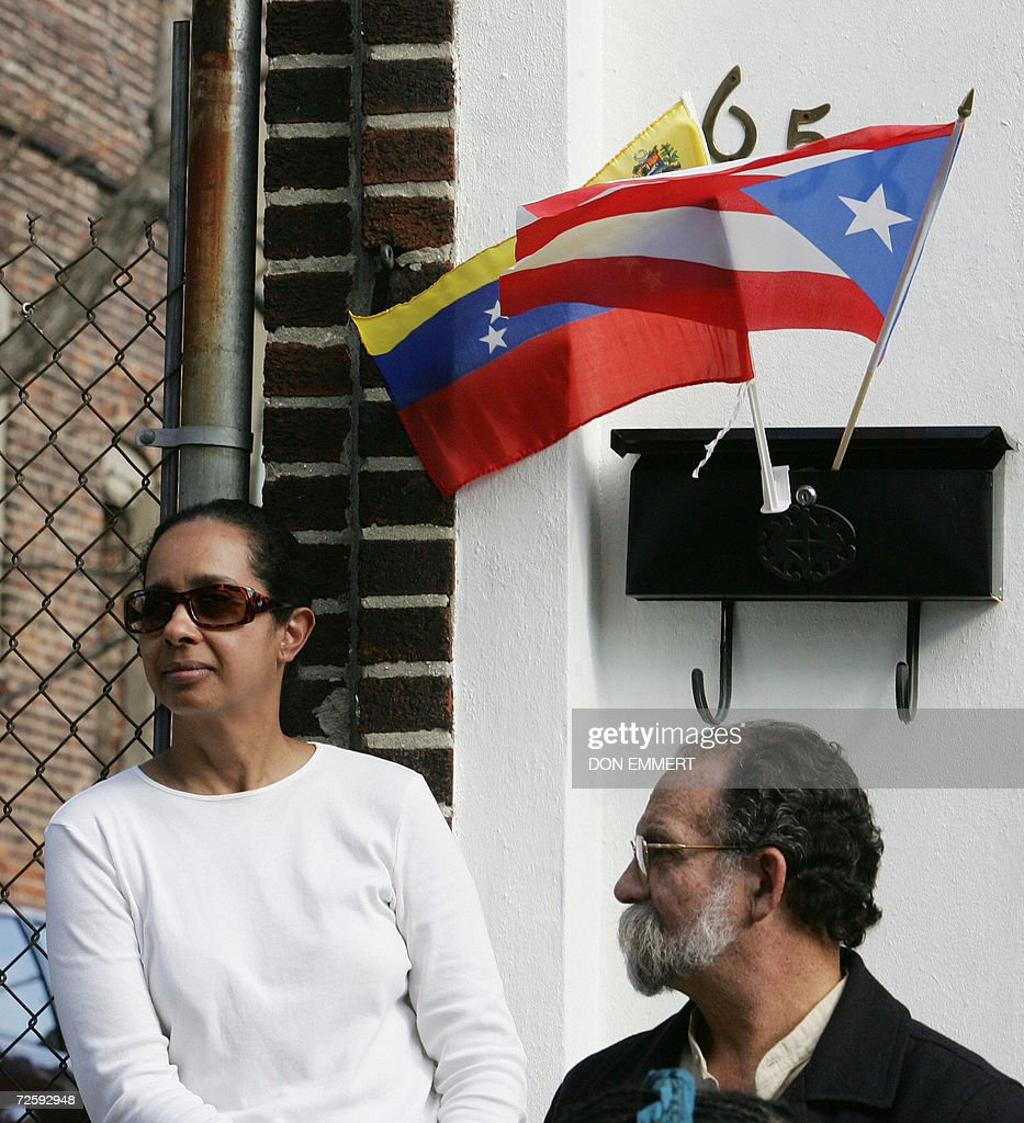 Next door neighbors of a cooperative apartment building, flying flags of Venezuela and Puerto Rico, listen to political speeches as low cost heating oil was being delivered to their cooperative apartment building 17 November, 2006 in the Bronx. The delivery was the initial low-cost heating oil of the CITGO-Venezuela heating oil program to the 60-unit building. AFP PHOTO/DON EMMERT