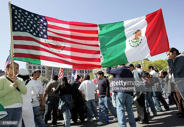 Protesters hold an American and Mexican flag that has been stitched together as they join the crowd of thousands of immigrants in a protest at Union...