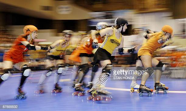 Roller derby skaters from the Manhattan Mayhem and the Bronx Gridlock speed through a corner during their season opening game 06 May at the Brooklyn...
