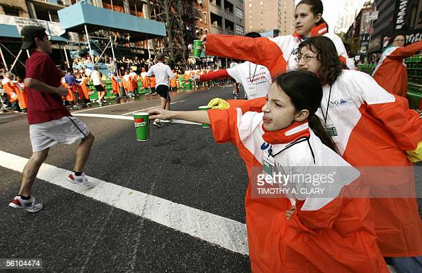 Runners are offered drinks as they make their way up First Avenue after entering Manhattan from the Queensborough Bridge on their way to the finish...